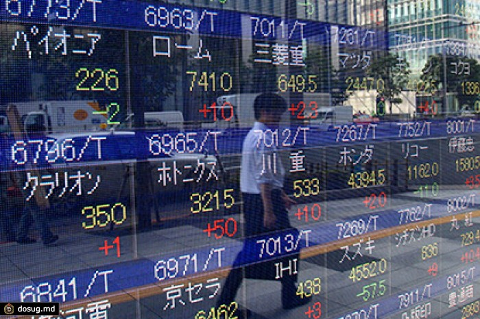 Un peatón pasa frente a un cartel de cotizaciones en Tokio el 11 de agosto del 2015. Los precios mundiales de las acciones cayeron el 12 de agosto después que China dejó caer el valor su divisa por segundo día después de una devaluación sorpresiva que conmovió los mercados financieros.(AP Foto/Ken Aragaki)
